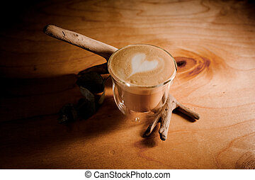 Transparent glass of a delicious hot coffee on the wooden table background