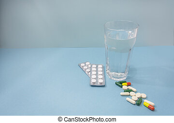 Transparent glass with water and pills on blue background. Selective focus, copy space. Taking medications, taking care of your health