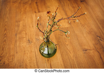 transparent long vase with branches on which buds bloom on the floor