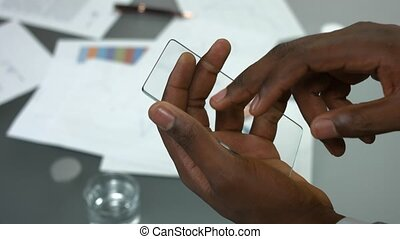 Transparent phone and male hands.
