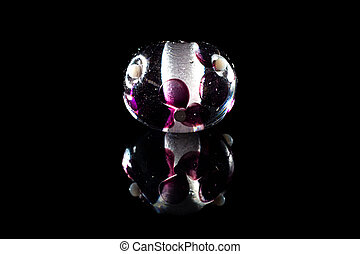 Transparent purple glass bead with reflection on black...