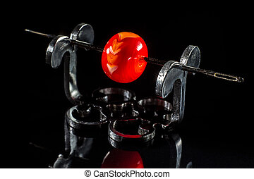 Transparent red glass bead on stand on black background