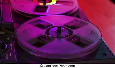 Transparent reels of retro magnetic tape spin on vintage tape recorder, illuminated by vibrant clubbing neon lights. Old music plays at a retro party. Nostalgia for 70, 80 years. Close up. Slow motion.