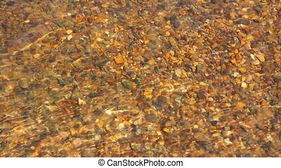 transparent river water in shallow with pebbles