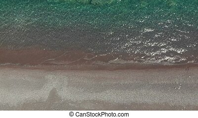 transparent sea water and waves rolling on sand beach -...