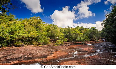 transparent cascade of wide shallow stream flows along brown stones among tropical forest under sunlight