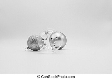 Transparent, silver and glittered grey Christmas balls on white background.