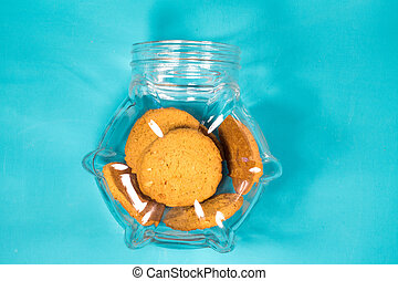 Transparent to open a jar with delicious cookies on wooden background close