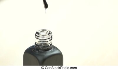 Transparent varnish dropping from brush, slow motion. Hand...