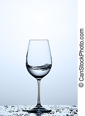 Transparent water wave in the wineglass while standing on the glass with water bubbles against light background.