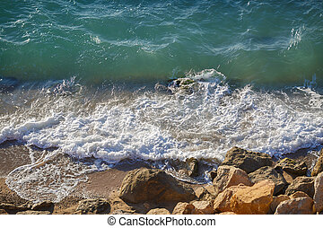 Transparent waves crash on rocky shore