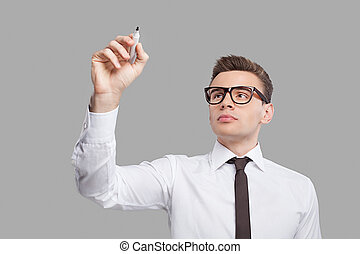 Transparent wipe board. Thoughtful young man in shirt and tie writing on the transparent wipe board while standing against grey background