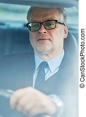 senior businessman driving car