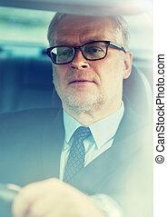 senior businessman driving car