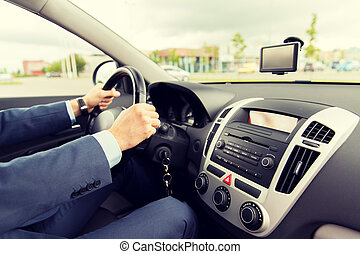 close up of young man in suit driving car