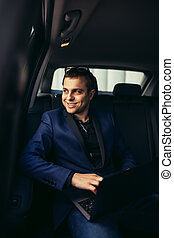 transport, business trip, safety concept - businessman driving on car back seat