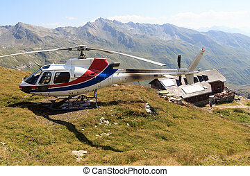 Transport helicopter landed near alpine hut and mountain...