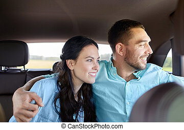 transport, road trip, travel, family and people concept - happy man and woman hugging in car and looking to window
