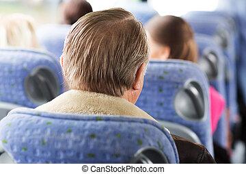 close up of senior man sitting in travel bus