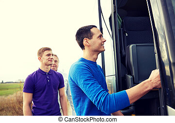 group of happy male passengers boarding travel bus