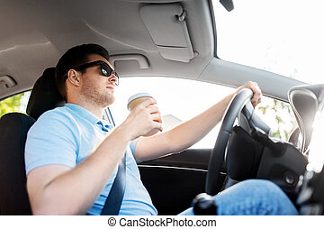 man or driver with takeaway coffee cup driving car