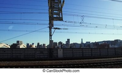 view to city from moving train or railway in japan -...