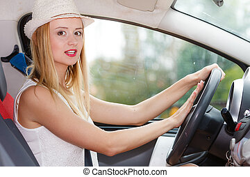Woman driving car with hand on horn button