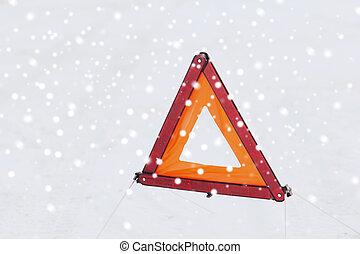 closeup of warning triangle on snow