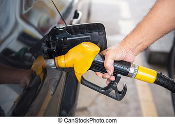 transportation concept - man pumping fuel in car at petrol...