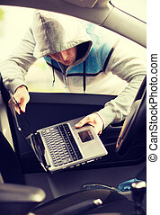 thief stealing laptop from the car - transportation, crime...