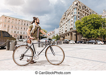Smart bearded man using a bicycle