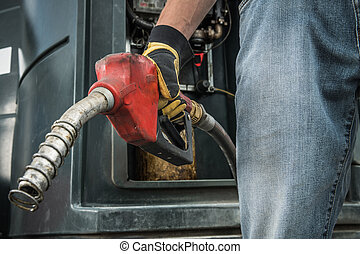 Trucker with Diesel Pump Nozzle in His Hand
