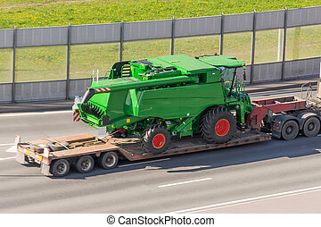 Transportation of agricultural machinery harvester on a trailer of a truck loading platform on a highway in the city.