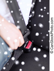 close up of man fastening seat belt in car