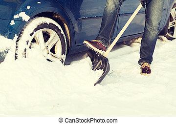 closeup of man digging up stuck in snow car -...