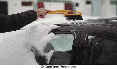 Transportation, winter, weather, people and vehicle concept - man cleaning snow from car with brush in living house district.