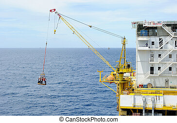Transporting workers at offshore - Workers are lifted by the...