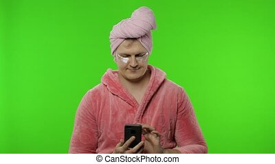 Transsexual man in bathrobe using mobile phone scared of ...