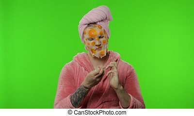 Transsexual man in bathrobe with face mask making manicure. ...