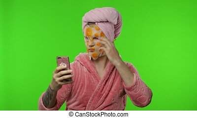 Transsexual man in bathrobe with face mask making selfies ...