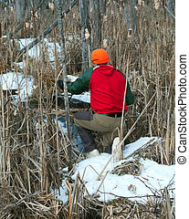 Trapper checking winter traps set for otter