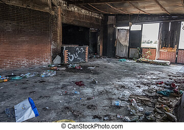 Trash and a mattress inside an abandoned burned building.