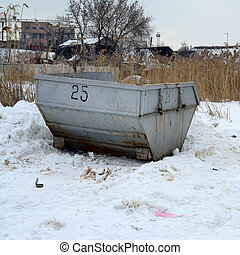Trash bin at the side of street in winter with lip garbage container winter snow. Metal container for household waste