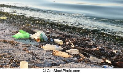 Trash on a beach with dirty polluted water