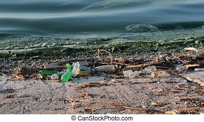 Trash on beach with surf of greenish polluted dirty water