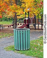 Trash can near playground in park in October.