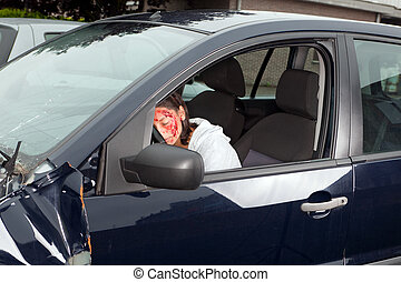 Young woman driver with bleeding face after car accident
