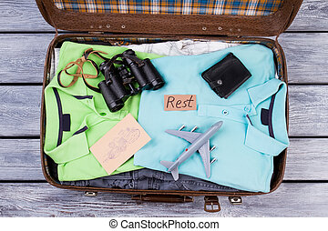 Travel accessories in opened suitcase.