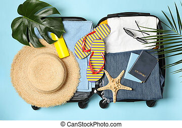 Travel accessories on blue background, top view