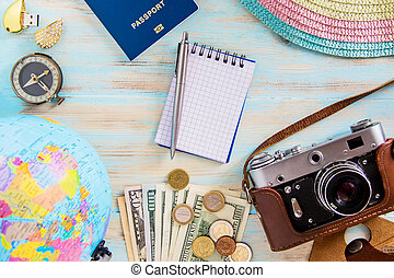 Travel accessories on blue wooden background old photocamera compass with passport and dollars